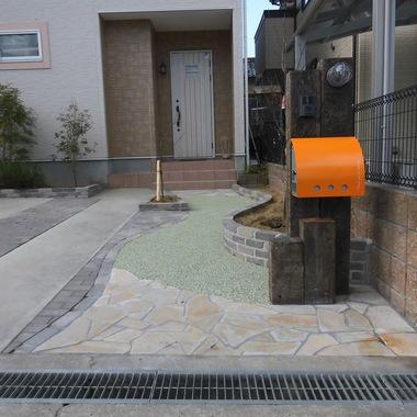 枕木の門柱にオレンジのポストとマリンライトで可愛く施工
